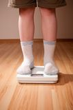 O menino mede o peso em escalas do assoalho fotografia de stock