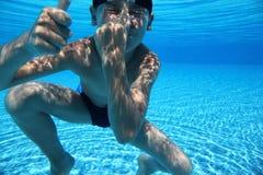 O menino mergulha sob a água na associação fotografia de stock royalty free
