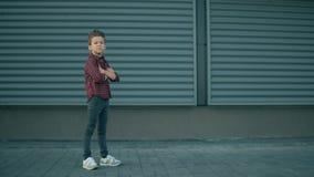 O menino modelo à moda bonito está levantando O menino sério da criança da forma está examinando à câmera o fundo azul moderno da vídeos de arquivo