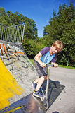 O menino monta o 'trotinette' em uma tubulação Fotos de Stock Royalty Free