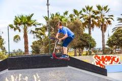 O menino monta seu 'trotinette' no parque do patim Fotos de Stock Royalty Free