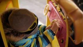O menino monta um carro do brinquedo no carrossel video estoque