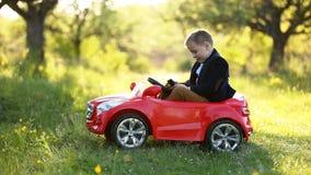 O menino monta um carro vermelho