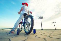 O menino monta uma bicicleta na margem fotos de stock royalty free