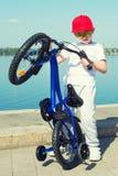 O menino monta uma bicicleta na margem fotos de stock
