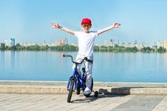 O menino monta uma bicicleta na margem imagens de stock