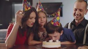 O menino morde um bolo de aniversário vídeos de arquivo