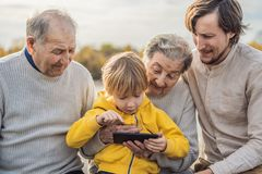 O menino mostra a foto no telefone a suas avós imagens de stock