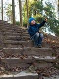 O menino mostra sua mão que senta-se nas escadas Imagens de Stock
