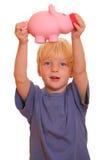 O menino mostra um banco piggy Fotos de Stock Royalty Free