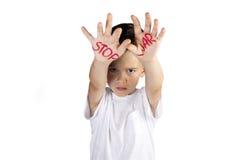 O menino mostra um sinal da guerra da parada da mão Fotografia de Stock Royalty Free