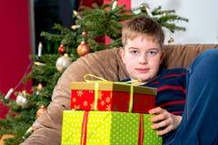O menino não está tão feliz com seus presentes de Natal Foto de Stock Royalty Free