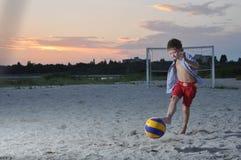 O menino na areia bate o pé de bola Imagem de Stock Royalty Free