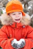 O menino na caminhada do inverno, mantem a neve Foto de Stock Royalty Free