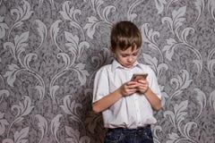O menino na camisa branca olha no telefone imagem de stock royalty free