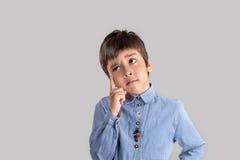 O menino na camisa pensa Fotografia de Stock