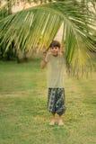 O menino na grama verde que guarda um ramo da palma Fotografia de Stock Royalty Free