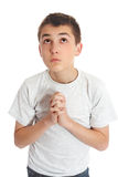 O menino na oração olha ao céu para respostas Foto de Stock