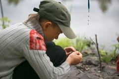 O menino na pesca veste a isca nas varas de pesca dos ganchos Foto de Stock