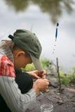 O menino na pesca veste a isca nas varas de pesca dos ganchos Fotografia de Stock