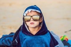 O menino na praia envolvida em uma toalha, molhou após nadar fotos de stock