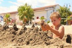 O menino na praia senta e modela montes da areia Imagem de Stock Royalty Free