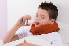 O menino na ucha bebe a água do vidro, as recomendações dos doutores em caso da doença imagens de stock