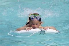 O menino nada na água azul brilhante Front View foto de stock