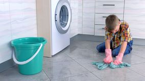 O menino nas luvas de borracha lava o assoalho na cozinha Deveres da casa da criança
