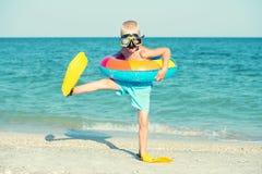 O menino nas máscaras e as aletas estão indo mergulhar no mar Mergulhador pequeno imagens de stock