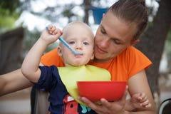 O menino nas mães dobra no acampamento, comendo na cadeira de dobramento de acampamento, tendo o divertimento no ar livre imagens de stock
