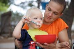 O menino nas mães dobra no acampamento, comendo na cadeira de dobramento de acampamento, tendo o divertimento no ar livre fotografia de stock