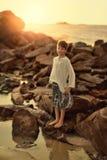 O menino nas rochas Fotografia de Stock