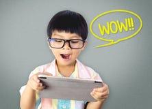 O menino nerdy asiático é emocionante com a tabuleta fotografia de stock royalty free