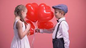 O menino no amor que dá a menina bonito coração-deu forma a balões, surpresa do dia de Valentim filme