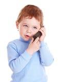 O menino no azul fala no telefone. Fotos de Stock