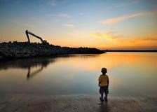 O menino no beira-mar aprecia seu tempo do crepúsculo Fotos de Stock Royalty Free