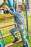 O menino no campo de jogos Fotografia de Stock Royalty Free