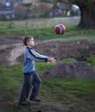 O menino no campo joga a bola Fotos de Stock Royalty Free