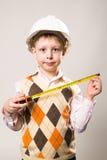 O menino no capacete da construção e uma fita métrica disponivel Imagens de Stock Royalty Free