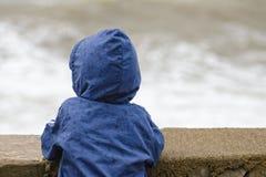 O menino no casaco azul com suportes da capa com sua parte traseira contra o cais na perspectiva do mar acena imagens de stock