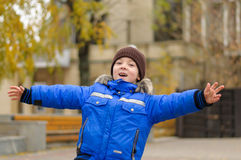 O menino no casaco azul espalhou seus braços Fotografia de Stock Royalty Free