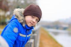 O menino no casaco azul inclina-se nos trilhos da cerca Foto de Stock
