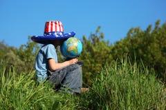 O menino no chapéu da bandeira americana senta e prende o globo fotografia de stock