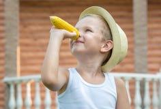 O menino no chapéu de palha come a espiga de milho no jardim Humor do milho imagens de stock