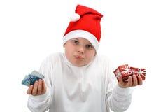 O menino no chapéu de Santa prende o dinheiro e o presente de Natal Fotografia de Stock Royalty Free
