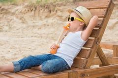 O menino no chapéu e nos óculos de sol de palha que encontram-se no vadio de madeira do sol na praia e para beber o suco fresco F imagens de stock