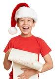 O menino no chapéu vermelho com rolo longo deseja a Santa - conceito do Natal do feriado de inverno Foto de Stock