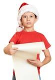 O menino no chapéu vermelho com rolo longo deseja a Santa - conceito do Natal do feriado de inverno Fotos de Stock