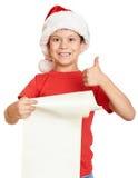 O menino no chapéu vermelho com rolo longo deseja a Santa - conceito do Natal do feriado de inverno Imagens de Stock